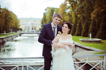 Wedding shot of bride and groom in park near river