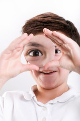 boy looks at through a magnifying glass
