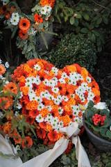 Frisches Grab mit herzförmigen Gesteck frischer Blumen