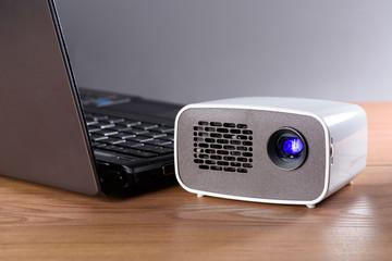 Akkubetriebener Mini Projektor mit einem Notebook auf einem Schr
