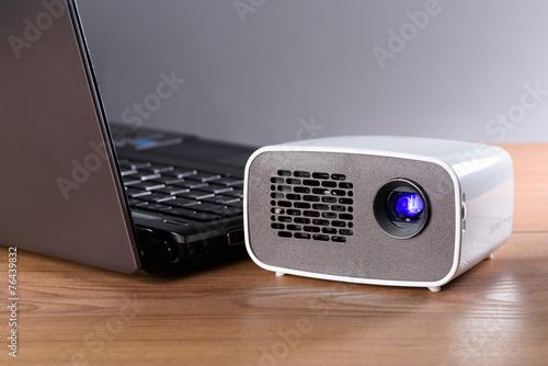 Akkubetriebener Mini Projektor mit einem Notebook auf einem Schr - 76439832