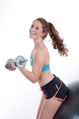 Junge sportliche Frau macht Hanteltraining auf Ball