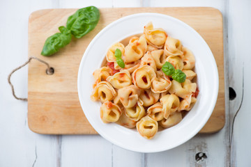 Glass plate with tortellini in tomato sauce, above view