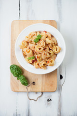 Italian tortellini with tomato sauce and green basil, above view