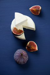 Sliced round cheese and fig fruits, dark blue wooden background