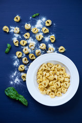 Raw tortellini with flour and green basil, view from above
