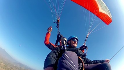 paragliding high above valley at bright blue sky