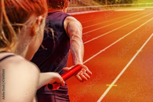 Leinwanddruck Bild Relay race handing over female male