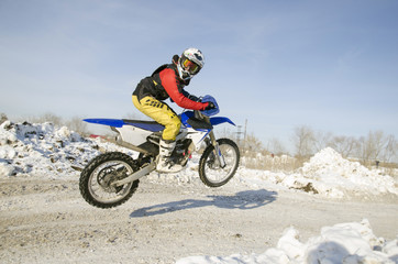 MX winter rider soars from a hill looking back