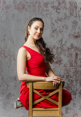 Young brunette girl in a red dress