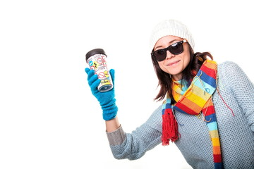 A girl in a knitted hat smiling and holding a thermo coffee on a