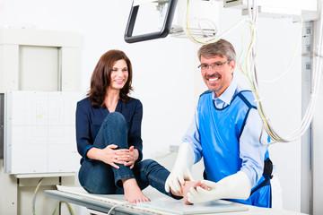 Arzt beim Röntgen von Bein der Patientin