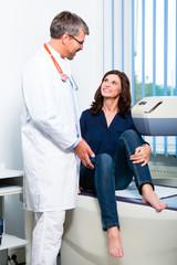 Arzt beim Ultraschall mit Patientin in Praxis