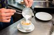 Barista in Cafe Bar gießt Milchschaum für Cappuccino - 76443096