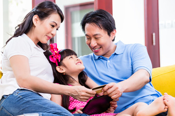 Chinese family online shopping with tablet computer