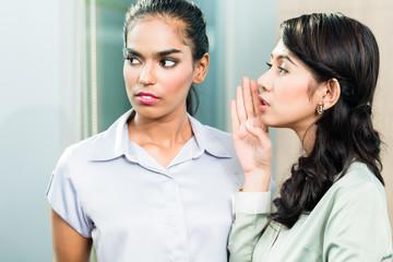Gossip in the office, woman whispering in ear