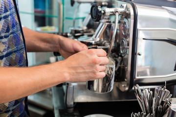 Bartender in Cafe Bar schäumt Milch auf