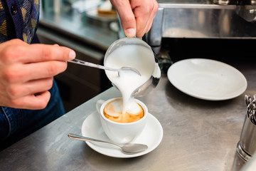 Barista in Cafe Bar gießt Milchschaum für Cappuccino