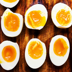 Hard boiled eggs, sliced in halves on wooden
