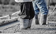 Concrete workers in heavy boots working in new wet concrete. - 76446867