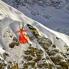 Red helicopter in flight in winter alps
