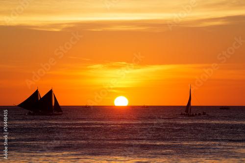 Leinwanddruck Bild Sailboats at sunset on a tropical sea. Silhouette photo.
