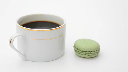 cup of coffee and macaroons rolling in