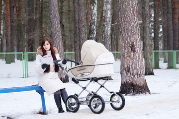 reading book young mother with baby buggy