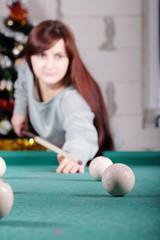 Beautiful woman playing billiard