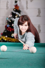 Beautiful woman playing billiard