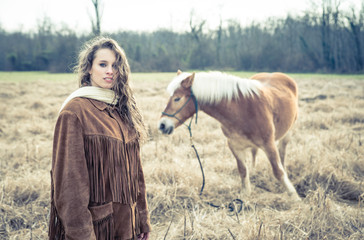 woman fashion portrait with horse in the background