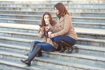 Two young friends drinking coffee and chatting