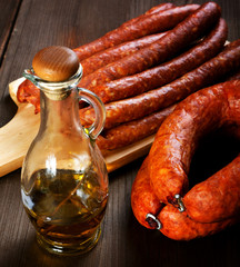 Bottle of olive oil and smoked sausage on a rural table