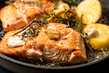 Grilled salmon fish with herbs, garlic and lemon