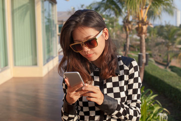 portrait oy young woman reading message on mobile phone use for