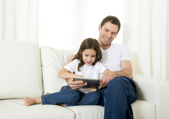 father on couch with little daughter using digital tablet pad