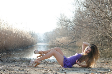 Woman in a purple dress on a dry reeds at the river