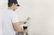 canvas print picture - Mann spachtelt Risse an Wand