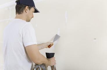 Mann spachtelt Risse an Wand