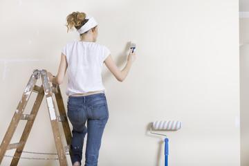 Frau streicht Wand auf Leiter