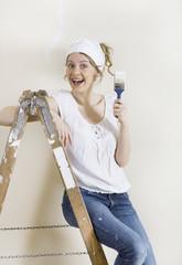 Frau mit Pinsel auf Leiter