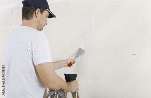 canvas print picture Mann spachtelt Risse an Wand