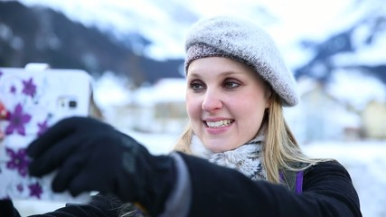 Blonde girl taking a selfie photo on the Swiss Alpine Alps