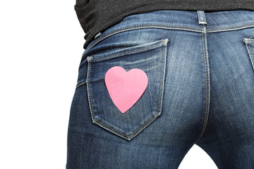 Girl's bum with paper heart on her jeans pocket