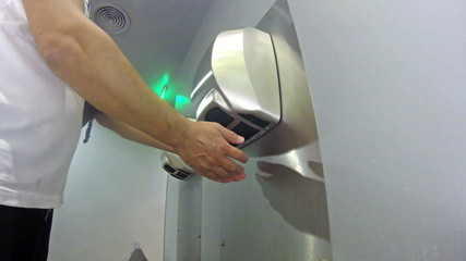 Drying off hands at toilet handdrier
