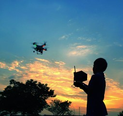 silhouette boy play drone / quadcopter  during sunrise or sunset