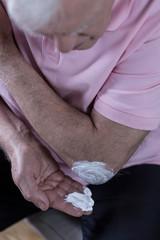 Senior man using ointment