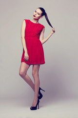 young elegant woman in red dress, fashion studio shot