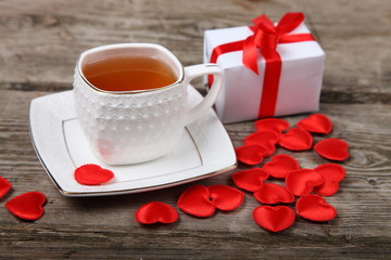 Cup of tea, gift and red hearts