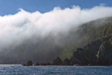 Rocky coastline, covered with a cloud of mist.